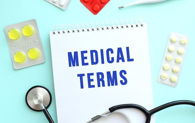 Medical terms라는 텍스트는 파란색 배경에 약인 청진기 옆에 있는 공책에 기록되어 있습니다.