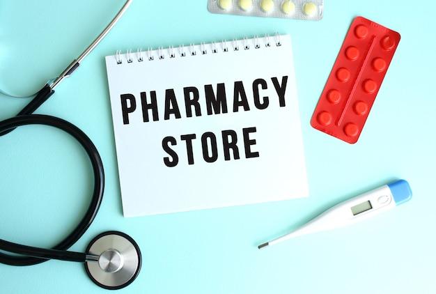 Pharmacy store라는 텍스트는 파란색 배경에 청진기와 알약 옆에 있는 흰색 메모장에 쓰여 있습니다. 의료 개념