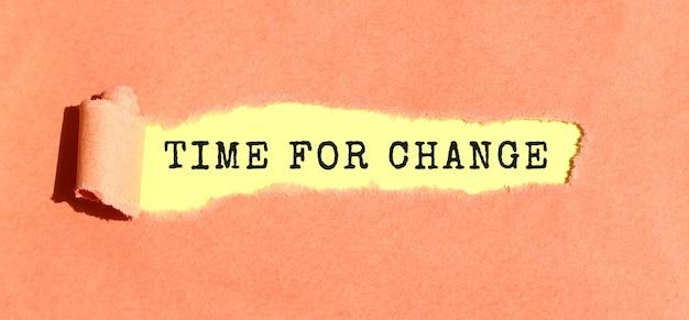찢어진 컬러 용지 뒤의 노란색 용지에 Time For Change라는 텍스트가 나타납니다. 평면도. 프리미엄 사진