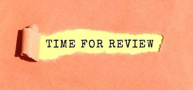 찢어진 컬러 용지 뒤의 노란색 용지에 time for review라는 텍스트가 나타납니다. 평면도.