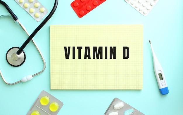 Vitamin d라는 텍스트는 파란색 배경에 약인 청진기 옆에 있는 노란색 공책에 쓰여 있습니다.