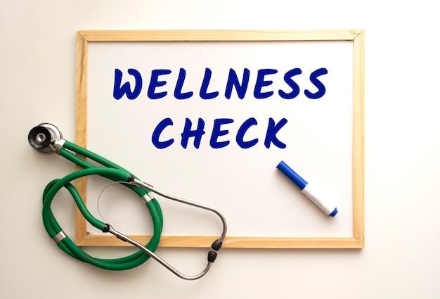 Wellness check 텍스트는 마커가있는 흰색 사무실 보드에 작성됩니다. 근처에는 청진기가 있습니다. 의료 개념.