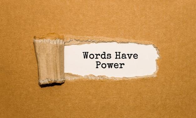 破れた茶色の紙の後ろに現れる「言葉は力を持っている」というテキスト