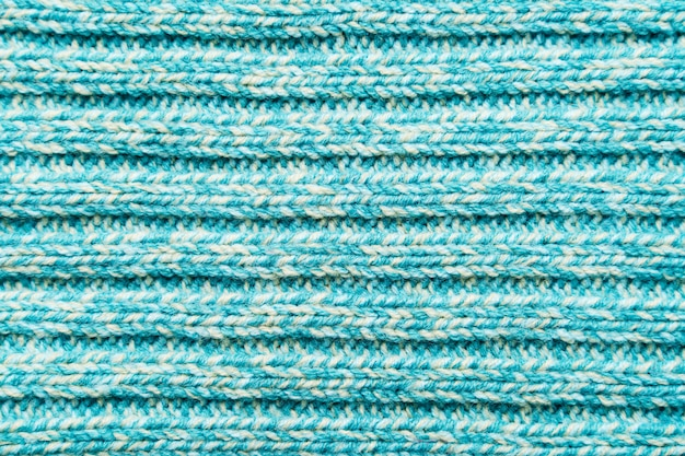 青いターコイズブルーのニット生地のテクスチャ。セーターの背景