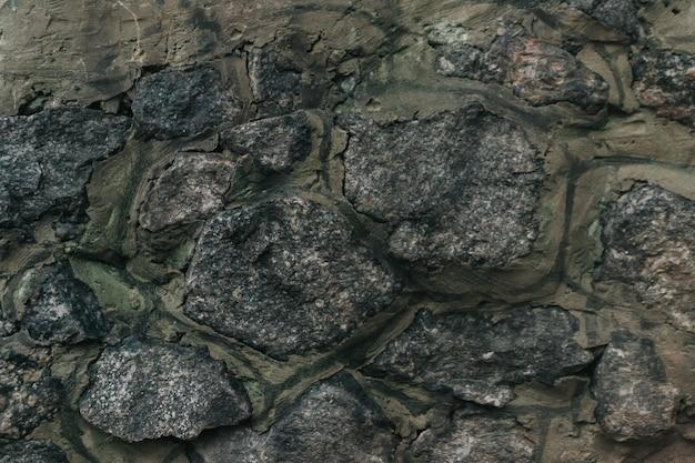자연적인 결함이 있는 돌 중세 성벽의 질감은 균열 틈새 칩 뒤를 긁습니다.