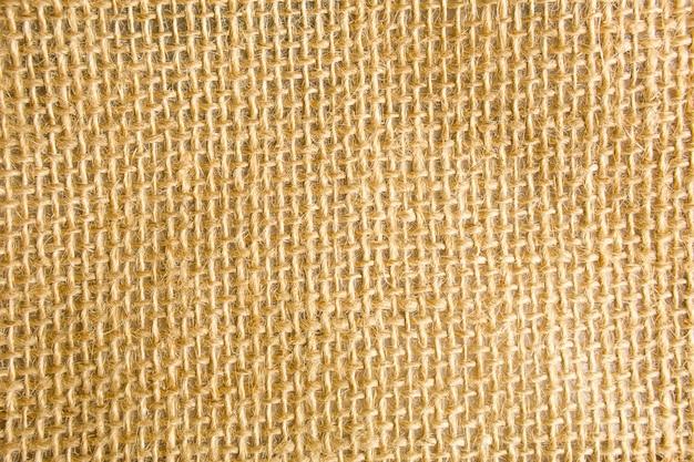 黄麻布の風合い、天然繊維製の檻の中のざらざらした織り、黄褐色。コピースペース、クローズアップ