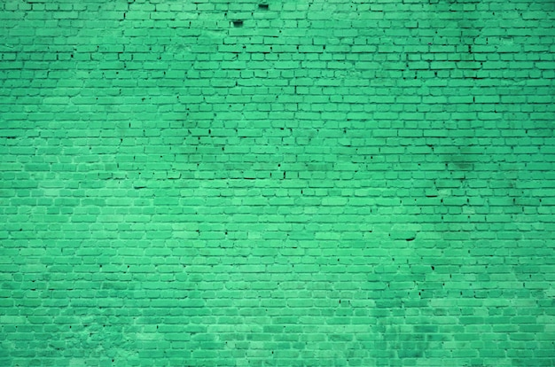 벽돌의 많은 행의 벽돌 벽의 질감은 녹색으로 칠해져 있습니다.