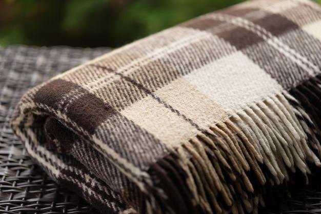 Фактура ткани шерстяного теплого коричневого бежевого клетчатого пледа с бахромой.