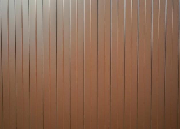 Фактура металлического забора из коричневого профиля с вертикальными линиями