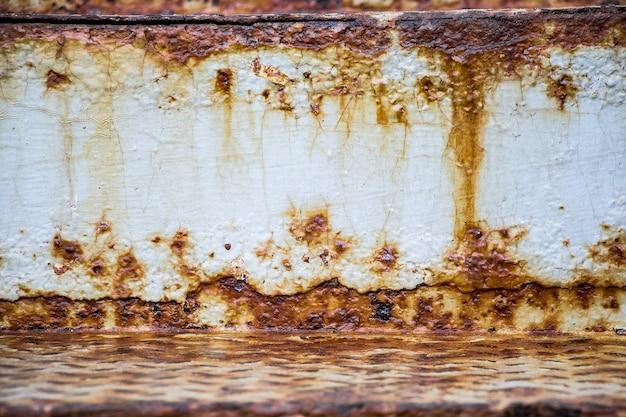 오래 된 녹슨 금속의 질감입니다. 흰색 바탕에 녹의 줄무늬를 닫습니다.