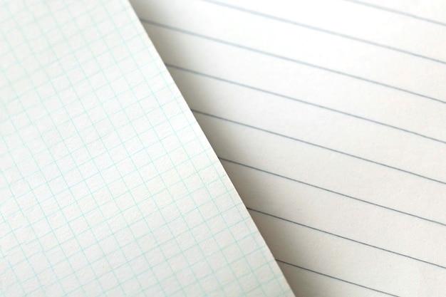 紙の背景の質感。灰色の背景のブロックから罫線入り用紙の空白のシート