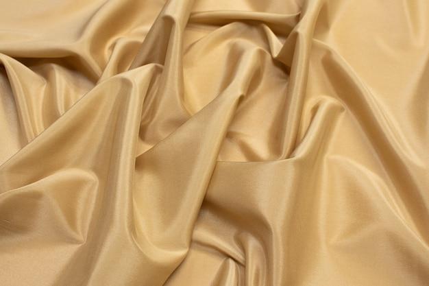 Текстура синтетической ткани светло-коричневая.
