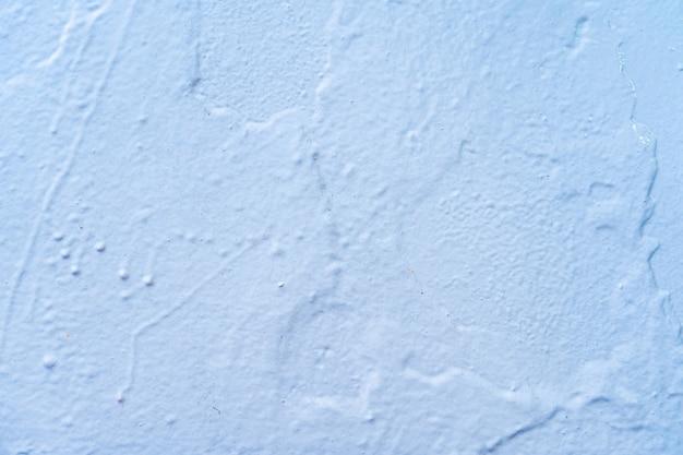 Фактура стены плохо прокрашена синей краской с подтеками.