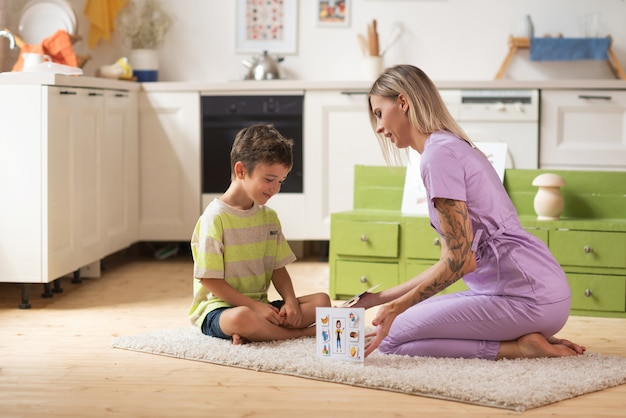 Терапевт играет с ребенком в развивающую игру, используя логические карточки.