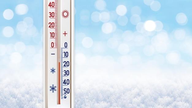 ぼやけた冬の背景の温度計は、氷点下15度を示しています
