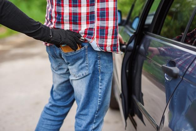 Вор в черной одежде и перчатках ворует кошелек с деньгами из кармана возле машины. карманные кражи на улице в дневное время.