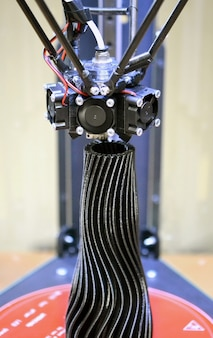 3축 3d 프린터는 검은색 꽃병 클로즈업 형태로 개체를 만듭니다.