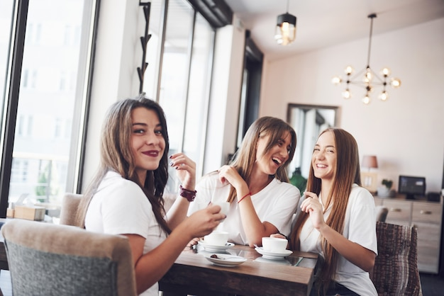 最高のガールフレンド3人が集まり、コーヒーとゴシップを飲みました。楽しんで笑っている女の子