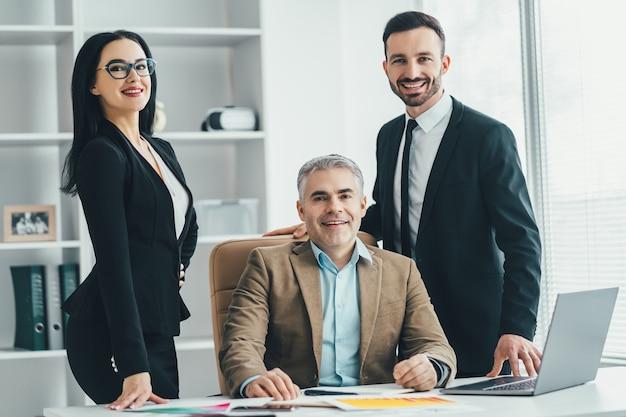 Трое деловых людей, стоящих возле стола