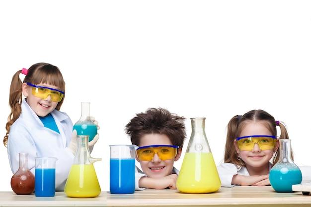 흰색 배경에 격리된 실험을 하는 화학 수업에서 화학자로 세 명의 귀여운 아이들