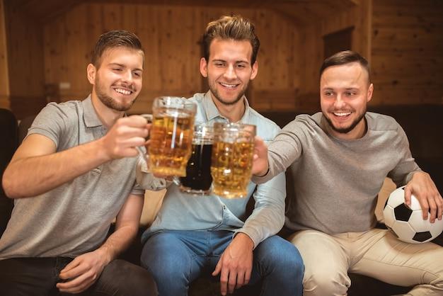 Трое друзей чокаются пивом
