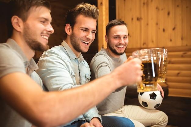 Три счастливых друга чокаются пивом