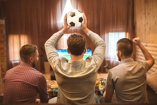 Трое мужчин смотрят футбол и держат мяч