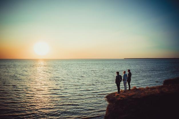 海の近くの山頂に立つ3人