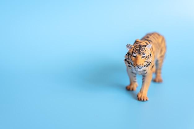 2022년을 상징하는 호랑이. 파란색 배경에 플라스틱 주황색 장난감 그림 호랑이입니다. 텍스트를 위한 공간
