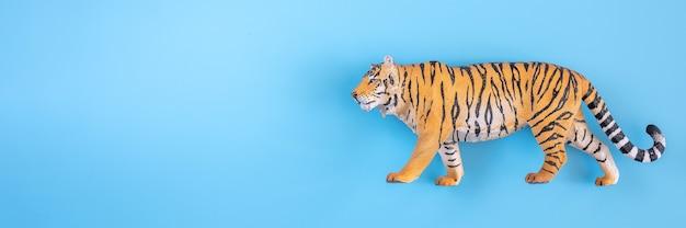 2022년을 상징하는 호랑이. 파란색 배경에 플라스틱 주황색 장난감 그림 호랑이입니다. 평면도. 텍스트를 위한 공간입니다. 배너