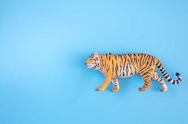 2022년을 상징하는 호랑이. 파란색 배경에 플라스틱 주황색 장난감 그림 호랑이입니다. 평면도. 텍스트를 위한 공간