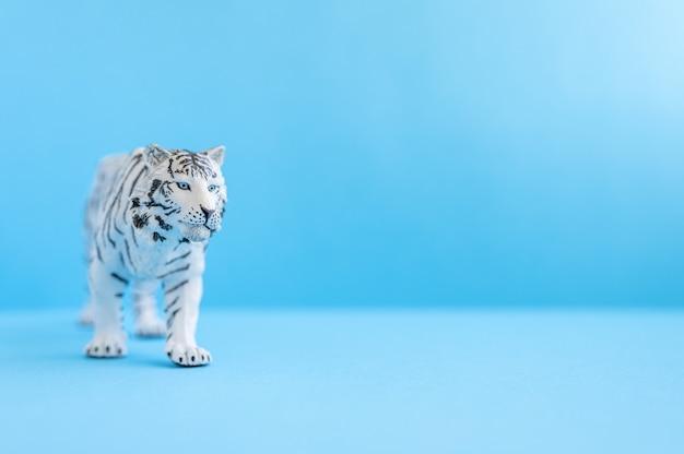 2022년을 상징하는 호랑이. 파란색 배경에 플라스틱 흰색 장난감 그림 호랑이입니다. 텍스트를 위한 공간