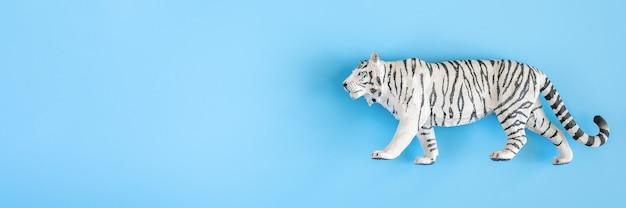 2022년을 상징하는 호랑이. 파란색 배경에 플라스틱 흰색 장난감 그림 호랑이입니다. 평면도. 텍스트를 위한 공간입니다. 배너