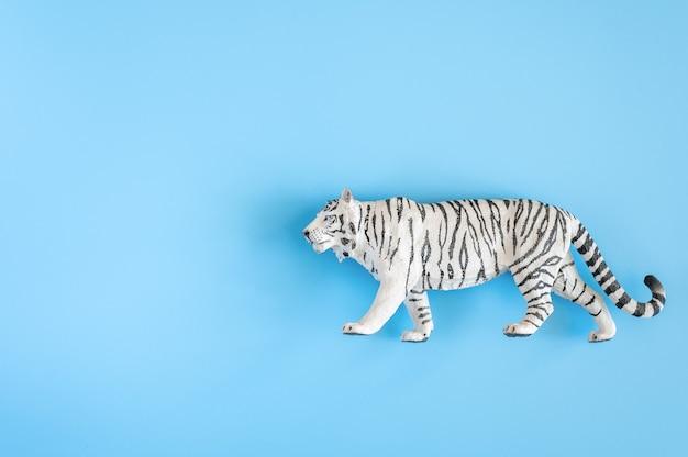 Тигр, символ 2022 года. пластиковая белая игрушка фигурка тигра на синем фоне. вид сверху. место для текста