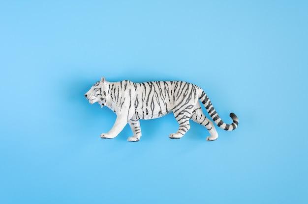 2022년을 상징하는 호랑이. 파란색 배경에 플라스틱 흰색 장난감 그림 호랑이입니다. 평면도