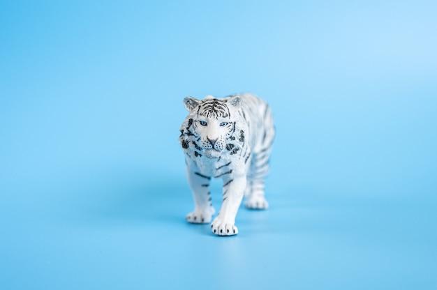 Тигр, символ 2022 года. пластиковая белая игрушка фигурка тигра на синем фоне