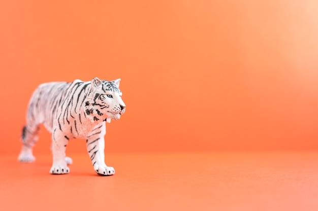 Тигр, символ 2022 года. пластиковая белая игрушка фигурка тигра на красном фоне. место для текста
