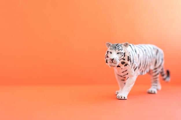 2022년을 상징하는 호랑이. 빨간색 배경에 플라스틱 흰색 장난감 그림 호랑이입니다. 텍스트를 위한 공간
