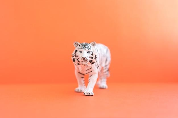 2022년을 상징하는 호랑이. 빨간색 배경에 플라스틱 흰색 장난감 그림 호랑이