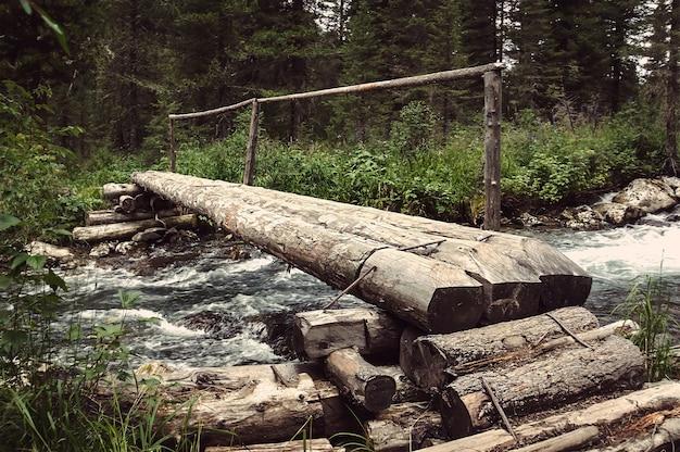 Бревенчатый мост проходит через лесную реку.