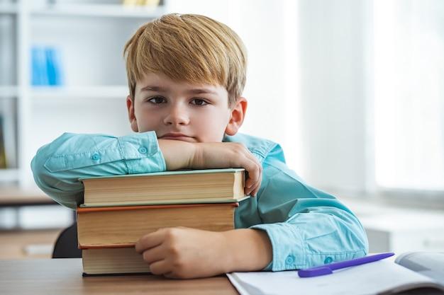 Уставший мальчик с книгами сидит за столом