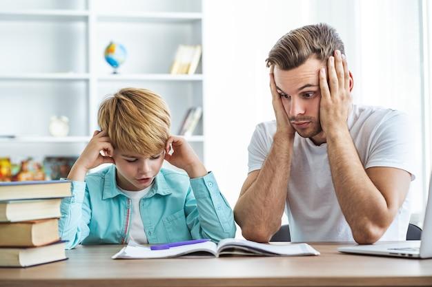Усталый отец и сын делают домашнее задание за столом