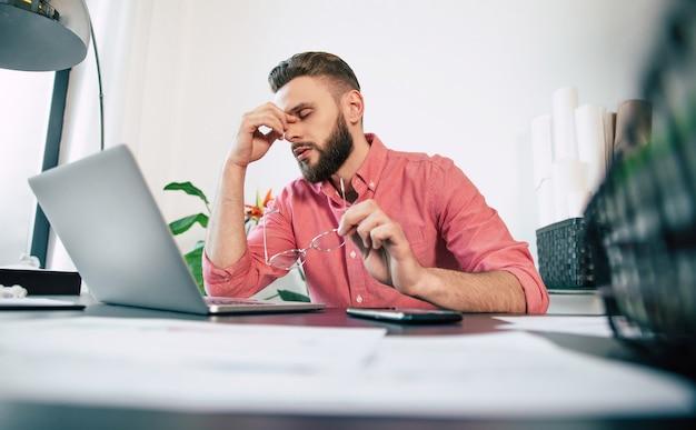 손에 안경을 든 피곤한 스트레스를 받거나 아픈 청년은 사무실에서 노트북으로 열심히 일하는 동안 쉬고 있습니다.