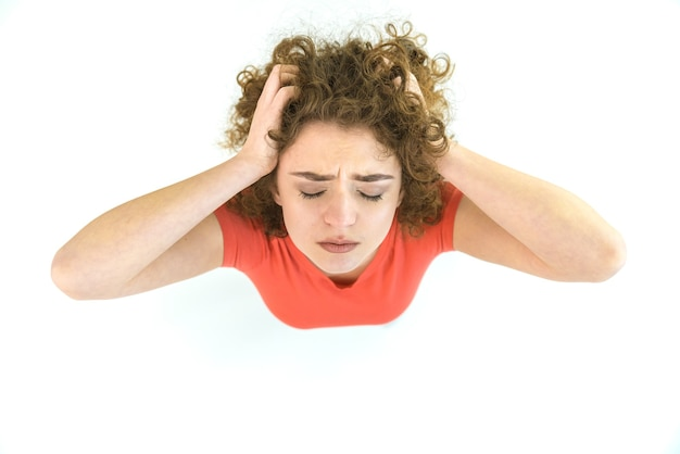 疲れた女性は白い背景の上に立っています。上から見る