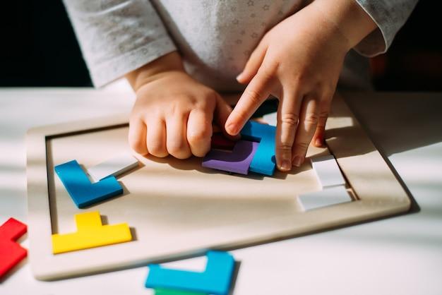 Малыш собирает на столе разноцветную головоломку.