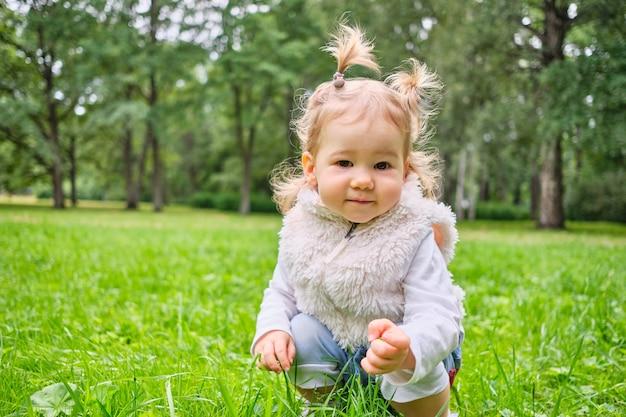 幼児は夏の公園を歩いて芝生に座っています。