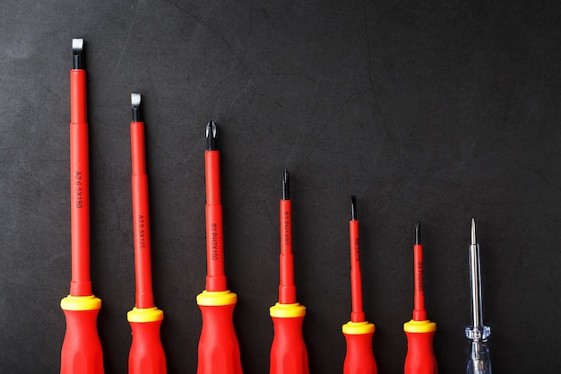 ツールは、空き領域のある黒い背景に並んだ赤いドライバーです。