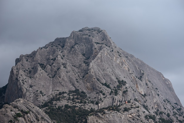 嵐の空の曇りの自然の背景の下で山の頂上