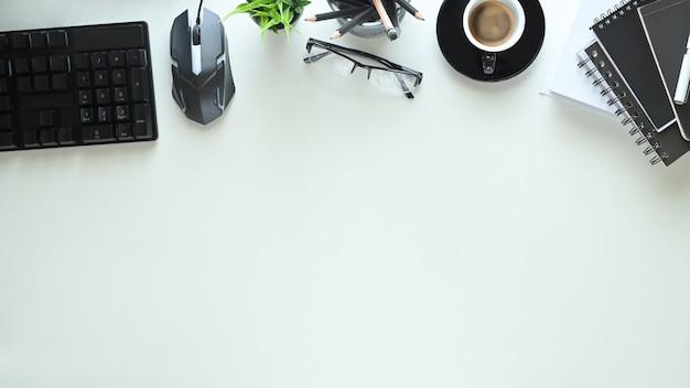 Вид сверху на белый рабочий стол окружен кофейной чашкой и оргтехникой.