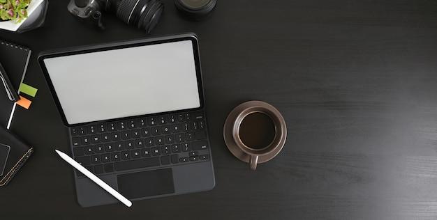 Вид сверху на черный стол, окруженный планшетом компьютера и фотографическим оборудованием.